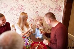 Happy mom and son at the Christmas or Thanksgiving dinner on a festive background. Family bonding concept. Young, pretty mother feeding happy son with sweets at Royalty Free Stock Images