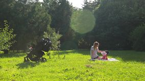 Young pretty mother in glasses and hat sits with her infant daughter on green lawn in pictorial city park with trees stock footage