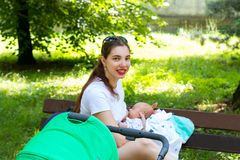 Portrait of a pretty nursing mother and baby, young mom is outside with her newborn child for stroller walk, breastfeeding public stock photo