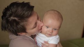 Young pretty mother kissing her little baby with love stock footage
