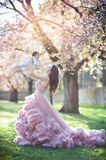Beautiful young mother carrying her little child at the background of blooming trees. royalty free stock photography
