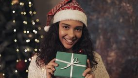 Young pretty mulatto woman at santas hat and decorative lights on her neck holding present box in her hands. She stock video footage