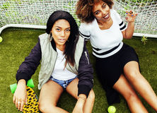 Young pretty multi ethnicity afro-american girls having fun on foothball field, fan club of swag teenagers. Close up Royalty Free Stock Image