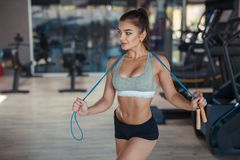 Attractive woman with jumping rope. Young pretty muscular woman standing with jumping rope in the gym Royalty Free Stock Photos