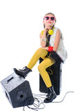 A young and pretty musician is sitting on loudspeakers Stock Images