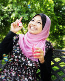 Young pretty muslim girl. Happy Young pretty muslim girl inflating colorful soap bubbles Royalty Free Stock Photos