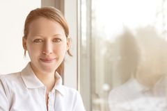 Young pretty nurse in front of a window, with reflection Royalty Free Stock Photo