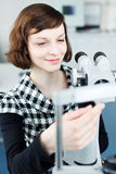 Young pretty optometrist using a slit lamp Stock Photo