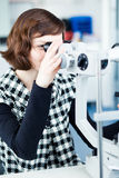 Young pretty optometrist using a slit lamp Stock Image
