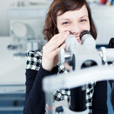 Young pretty optometrist using a slit lamp Stock Images