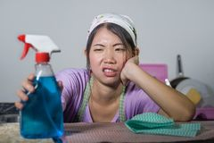 Young pretty overworked and frustrated Asian Chinese service maid woman working domestic cleaning and washing home kitchen stresse. D and upset in housework and royalty free stock images