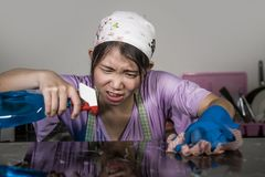 Young pretty overworked and sad Asian Chinese service maid woman working domestic cleaning and washing home kitchen angry upset an. D frustrated in housework and stock image