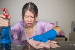 Young pretty overworked and sad Asian Chinese service maid woman working domestic cleaning and washing home kitchen angry upset an. D frustrated in housework and stock photo