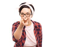 Young pretty pin-up girl showing watching you gesture. Portrait of young pretty pin-up girl wearing glasses showing watching you gesture isolated on white stock images