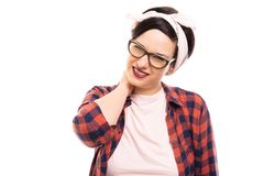 Young pretty pin-up girl wearing glasses showing neck pain gesture. royalty free stock photography