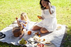 Young pretty pregnant brunette woman having fun with her daughter on picnic on green grass in park, lifestyle people