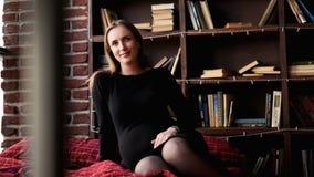 Young pretty pregnant woman in black dress in studio. Loft interior stock images