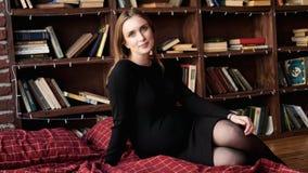 Young pretty pregnant woman in black dress in studio. Loft interior stock photos