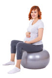 Young pretty pregnant woman doing exercises on fitball isolated. On white background Stock Image