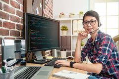 Wearing headphone and looking to screen. Young pretty programmer wearing head phone and looking to screen with a confident smile royalty free stock images