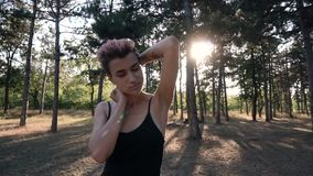 Young Pretty Punk Girl in Collar and Black Cloth with Pink Hair walking in Pine Forest at Sunset Time. Young Pretty Pierced Punk Girl in Collar and Black Cloth stock footage
