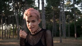 Young Pretty Punk Girl in Collar and Net. Pink Hair Girl walking in Pine Forest at Sunset Time. Young Pretty Pierced Punk Girl in Collar and Net. Pink Hair Girl stock footage