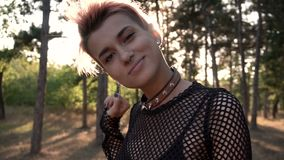 Young Pretty Punk Girl in Collar and Net. Pink Hair Girl walking in Pine Forest at Sunset Time. Young Pretty Pierced Punk Girl in Collar and Net. Pink Hair Girl stock video footage