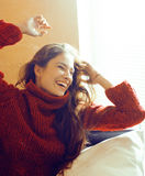 Young pretty real woman in red sweater and scarf all over her fa Stock Image