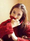 Young pretty real woman in red sweater and scarf all over her fa Royalty Free Stock Image