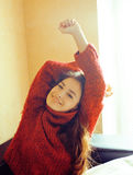 Young pretty real woman in red sweater and scarf all over her fa Stock Photos