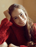 Young pretty real woman in red sweater and scarf all over her face smiling at home, winter positive Royalty Free Stock Photography