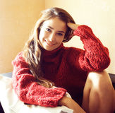 Young pretty real woman in red sweater and scarf all over her face smiling at home, winter positive, lifestyle people Stock Photo