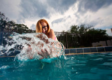 Young Pretty Red Haired Woman swimming and playing in an i pool Stock Photos