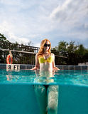 Young Pretty Red Haired Woman swimming and playing in pool Stock Photography