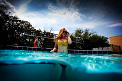 Young Pretty Red Haired Woman swimming and playing in a pool Stock Photos