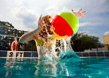 Young Pretty Red Haired Woman swimming and playing in a pool. Young Pretty Red Haired Woman swimming and playing in an in-ground Pool Royalty Free Stock Photos