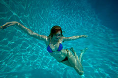 Young Pretty Red Haired Woman swimming and playing in a pool Royalty Free Stock Images