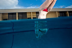 Young Pretty Red Haired Woman swimming and playing in a pool Royalty Free Stock Photography