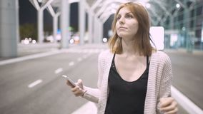 Young pretty red-haired woman writing message using her smatphone. Urban night background. Young pretty red-haired woman writing message using her smatphone stock footage