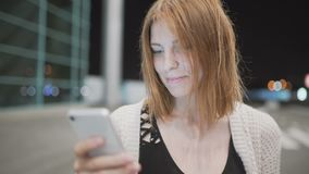 Young pretty red-haired woman writing message using her smatphone. Urban night background. Young pretty red-haired woman writing message using her smatphone stock video
