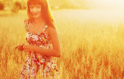 Young pretty red woman at the field Stock Image