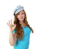 Young pretty redhead girl in cap shows ok gesture royalty free stock photo