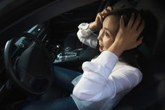 Young pretty scared woman in the car. Young pretty asian scared woman driving in the car royalty free stock photos