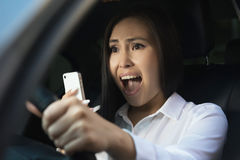 Young pretty scared woman in the car. Young pretty asian scared woman driving in the car stock photos