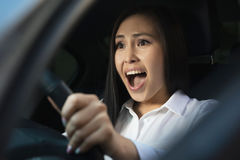 Young pretty scared woman in the car. Young pretty asian scared woman driving in the car royalty free stock images