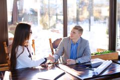 Young secretary refusing in handshaking with boss at cafe. royalty free stock photos