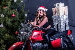 Young Pretty Sexy Girl In Santa Hat Sits On A Red Motorcycle In Christmas Decor With Gift Boxes Royalty Free Stock Image