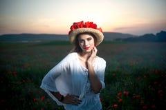Young pretty woman in poppy fields stock photo