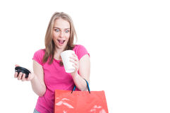 Young pretty shopaholic holding shopping bags and espresso Stock Photo