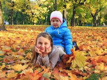 Young pretty sisters lay on yellow leaves in autumn park. Happy childhood royalty free stock image